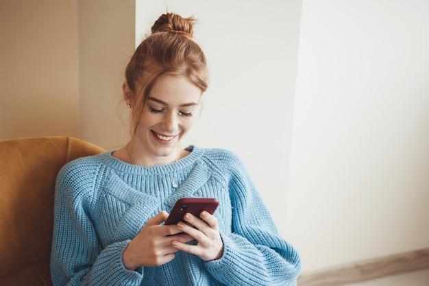 Gember dame met sproeten lacht tijdens het chatten op mobiel thuis blauwe gebreide trui dragen