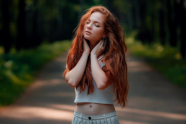 Gember jonge mooie vrouw poseren in een groen bos