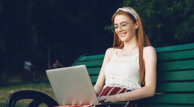 Gember kaukasische dame met sproeten glimlacht tijdens het typen op de laptop zittend op het bankje in het park