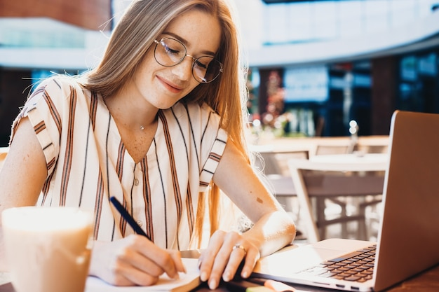 Gember kaukasische student met sproeten enkele aantekeningen maken tijdens het werken met een computer in een restaurant