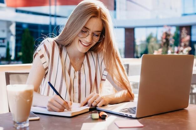 Gember kaukasische student met sproeten schrijft iets in haar notitieboekje terwijl ze een kopje koffie drinkt en haar laptop gebruikt