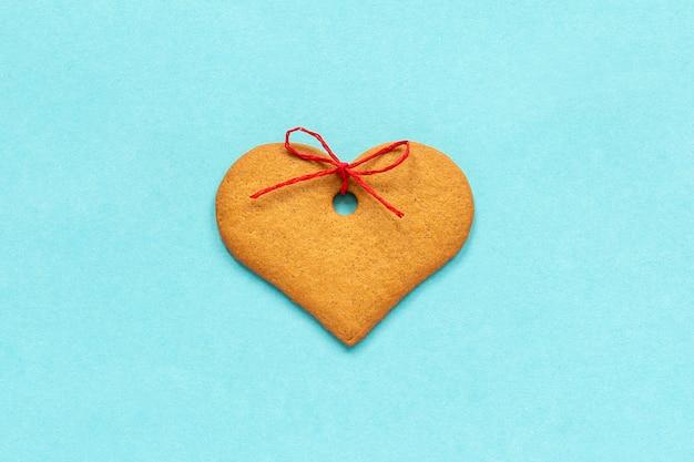 Gember koekjes hartvormig versierd met een strik op een blauwe achtergrond valentine-kaart