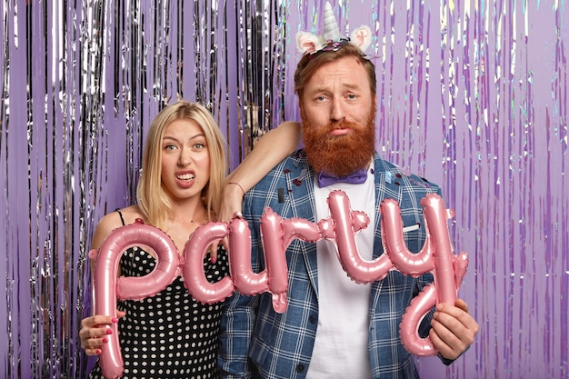 Gember man en blonde vrouw op feestje met ballonnen