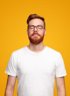 Gember man in glazen en wit t-shirt ogen sluiten en ademen tijdens het mediteren tegen gele achtergrond