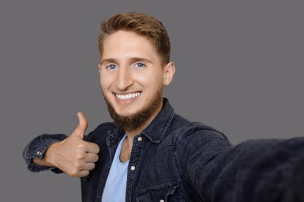 Gember man met baard gebaart het soortgelijk teken en maakt een selfie op grijze studiomuur