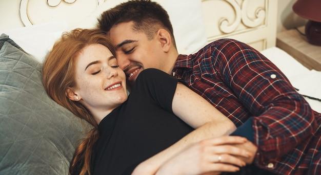 Gember meisje met sproeten in bed liggen met haar minnaar omarmen en samen glimlachen