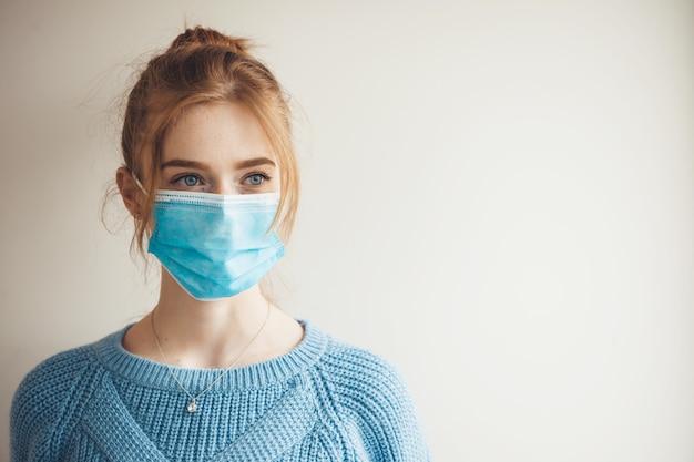 Gember meisje met sproeten medische masker en gebreide blauwe trui dragen is poseren op een witte studio muur met vrije ruimte