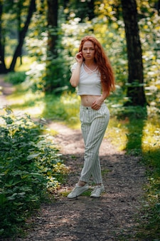 Gember mooie vrouw in casual outfit poseren in het bos