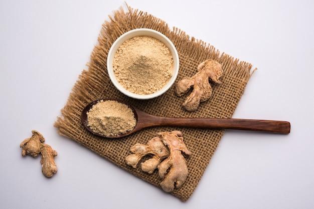 Gember- of adrak-poeder met gedroogd geheel, ook bekend als sunth of sonth in india, over humeurige achtergrond. selectieve focus