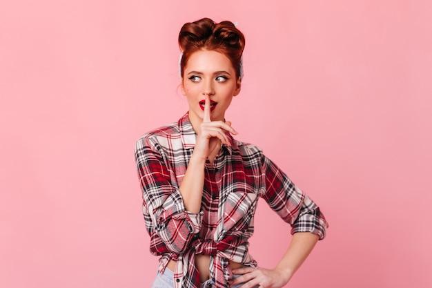 Gember pinup meisje dat stilte vereist. studio shot van vrouwelijk model in geruit overhemd geïsoleerd op roze ruimte.