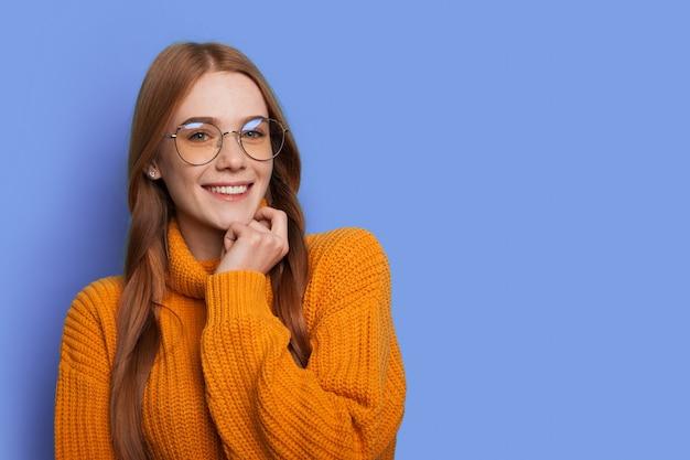 Gember vrouw met rood haar lacht naar camera met bril op een blauwe studiomuur met vrije ruimte
