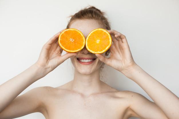 Gember vrouw met sproeten bedekt haar ogen met gesneden sinaasappel en glimlach op een witte muur met blote schouders