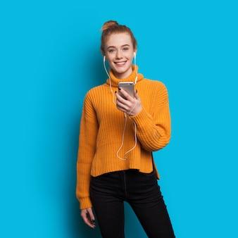 Gember vrouw met sproeten in een gele trui luistert naar mijmering via oortelefoons en mobiel op een blauwe muur