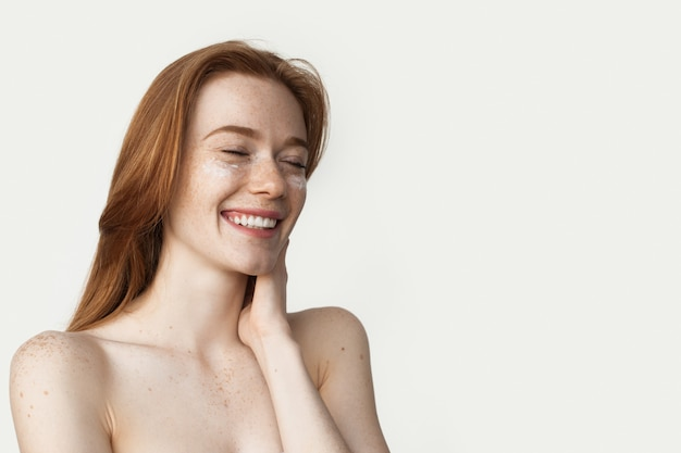 Gember vrouw met sproeten is room toe te passen op haar gezicht lachend op een witte muur met blote schouders