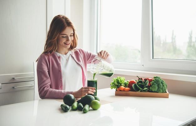 Gember vrouw met sproeten maakt vers groen groentesap thuis het in een glas te zetten