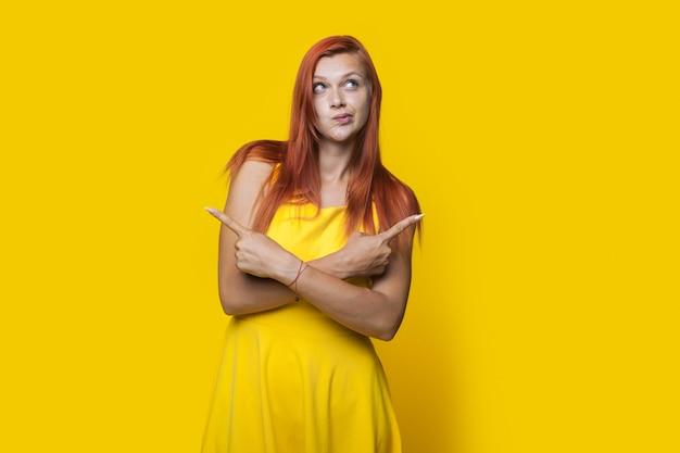 Gember vrouw met sproeten wijst naar gele vrije ruimte in de buurt van haar en denkt aan iets terwijl ze een mooie zomerjurk draagt