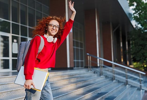 Gember vrouwelijke student met rugzak zwaaien naar vrienden