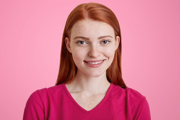 Gember vrouwtje met een aangename glimlach, heeft een sproetige huid, is blij om gefotografeerd te worden, kleedt zich in een roze trui