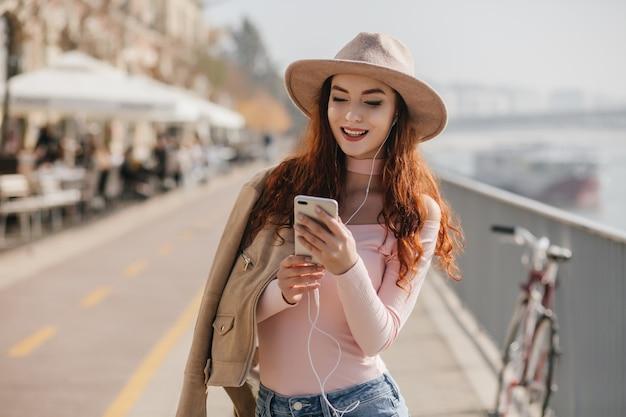 Gember witte vrouw die lacht tijdens het lezen van mobiel bericht