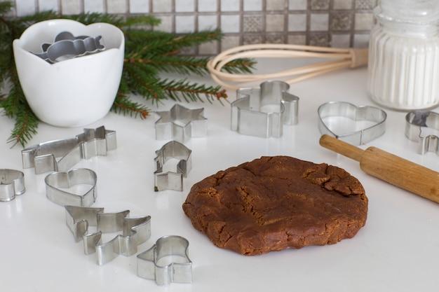 Gemberdeeg, deegrol, vuren takken, bloem op de keukentafel - fase voor het bereiden van koekjes