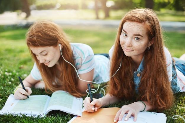 Gemberhaar starend met opgetrokken wenkbrauwen en schattige glimlach, liggend op gras in stadspark met zus, oortelefoons delen om samen naar muziek te luisteren en huiswerk te maken. levensstijl en mensen concept