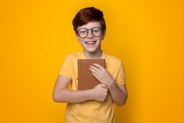 Gemberjongen die boek omhelst en een bril draagt