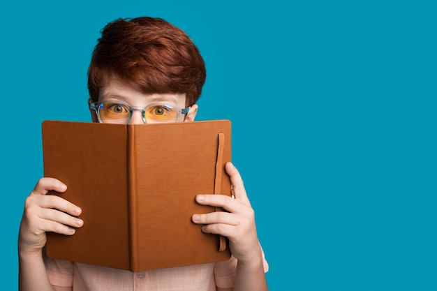 Gemberjongen met bril verbergt zich achter een boek en kijkt naar de camera op een blauwe studiomuur met vrije ruimte