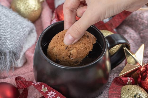 Gemberkoekje onderdompelen in een drankje op de tafel bedekt met kerstversieringen