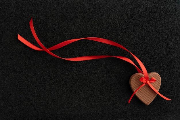 Gemberkoekjes in vorm van harten met rood lint op zwarte achtergrond.