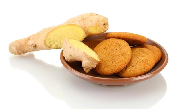 Gemberkoekjes met verse gemberwortel die op wit wordt geïsoleerd