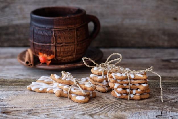 Gemberkoekjes met zelfgemaakte suikerglazuur en een grote koffiemok op een houten tafel