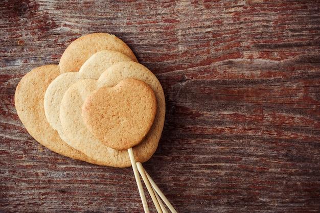Gemberkoekjes op een stok in de vorm van harten op een houten achtergrond. bovenaanzicht