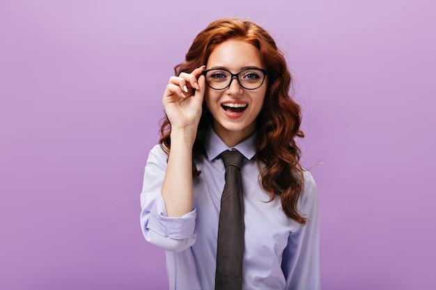 Gembermeisje met bril kijkt in camera op paarse muur
