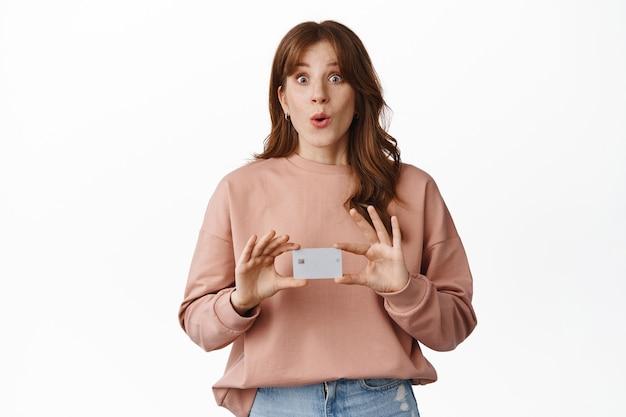 Gembermeisje ziet er opgewonden uit, toont creditcard in handen, praat over bank-app, speciale aanbieding, staat op wit in vrijetijdskleding