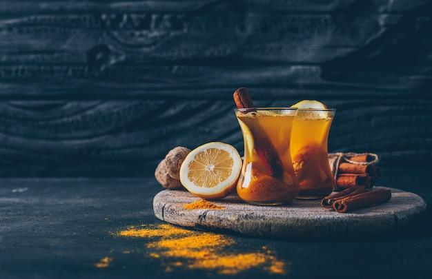 Gemberpoeder in theekoppen met citroen, gember en droog kaneel zijaanzicht op een donkere gestructureerde achtergrondruimte voor tekst