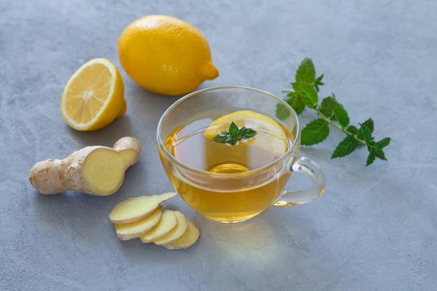 Gemberthee in glazen beker met citroen en munt op stenen tafel