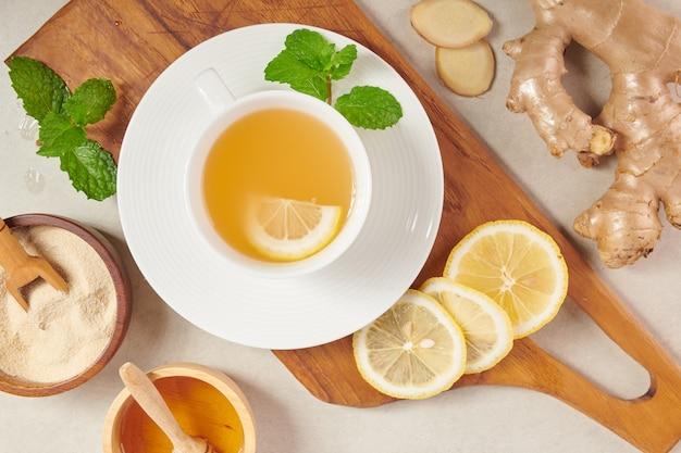 Gemberthee-ingrediënten, gezonde troostende en verwarmende thee onder eenvoudig recept. gemberthee en ingrediënten - citroen, honing. bovenaanzicht. plat leggen. vers uit de biologische tuin van thuisgroei. voedsel concept.