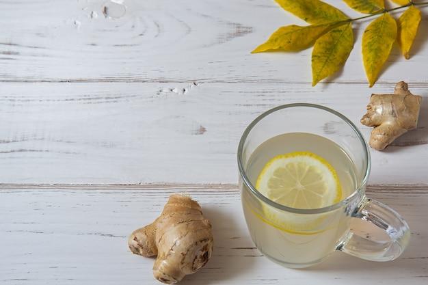 Gemberthee met citroen en bladeren op een witte lijst