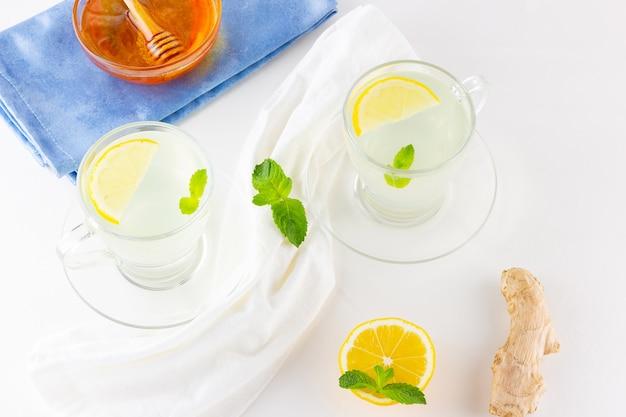 Gemberthee met citroen en munt in glazen mokken