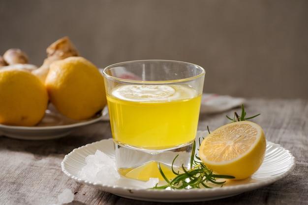 Gemberthee met citroen, gemberwortel en rozemarijn op houten tafel. kleine glazen doorzichtige kan met warme drank.