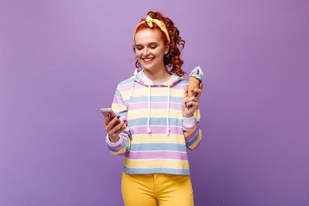 Gembervrouw in gele haardressing met glimlach is aan het chatten in smartphone en houdt blauw ijs vast