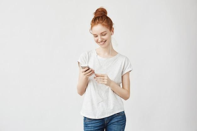 Gembervrouw met sproeten in hoofdtelefoons glimlachen die telefoon bekijken.