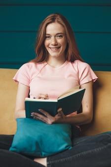 Gembervrouw met sproeten ligt in bed en leest een boek glimlachend in de camera