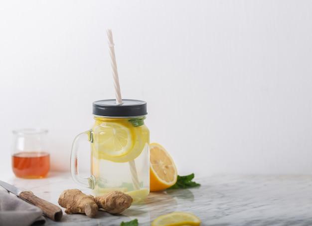 Gemberwater in glazen pot met citroen en honing, horizontale oriëntatie, witte tafel, kopie ruimte