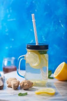 Gemberwater in glazen pot met citroen en honing op blauwe, verticale oriëntatie