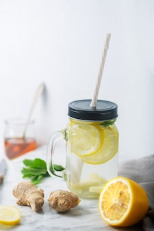 Gemberwater in glazen pot met citroen en honing, verticale oriëntatie, witte tafel