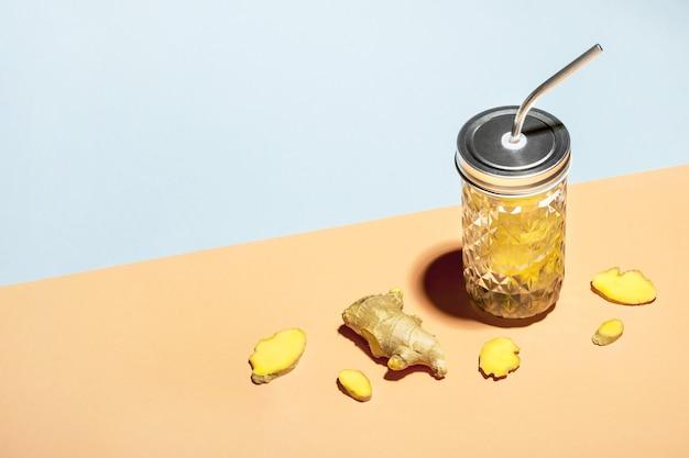 Gemberwater in stijlvolle pot met metalen rietje op geometrische papieren achtergrond en gemberplakken, isometrisch aanzicht.