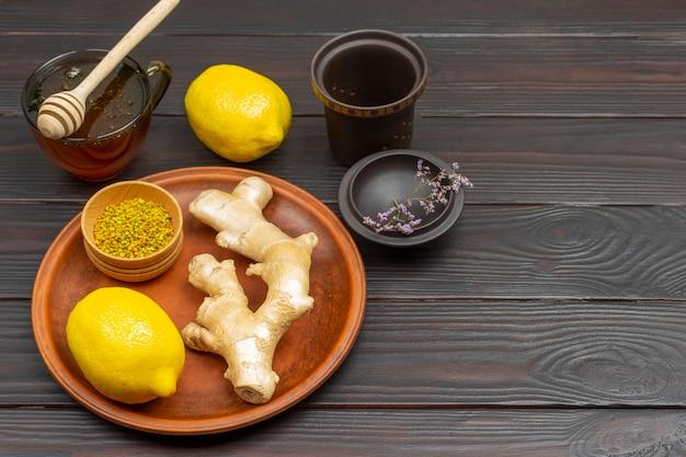 Gemberwortel, citroen en stuifmeel in kom op keramische plaat. honing in beker en citroen op tafel. donkere houten achtergrond. ruimte kopiëren. bovenaanzicht