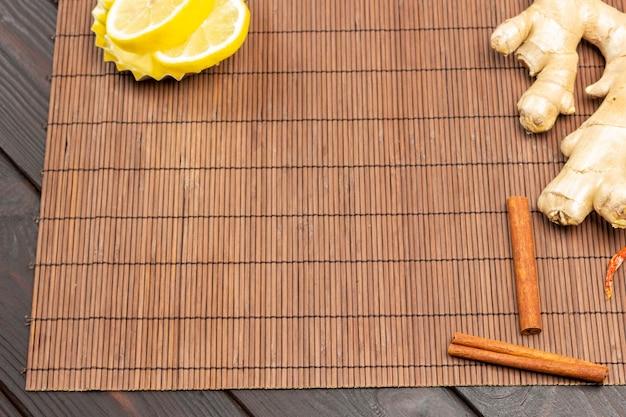 Gemberwortel en kaneelstokjes op tafel. citroenpartjes in kom. ruimte kopiëren. houten achtergrond. bovenaanzicht