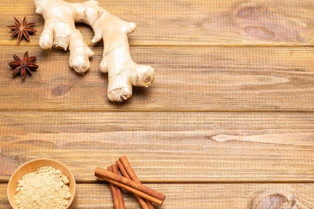 Gemberwortel en kaneelstokjes op tafel. droog gemberpoeder in kom. houten achtergrond. bovenaanzicht. ruimte kopiëren